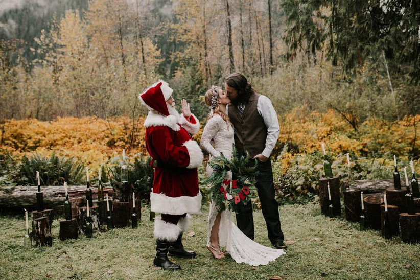 bride and groom kiss while wedding officiant in santa claus costume stands nearby