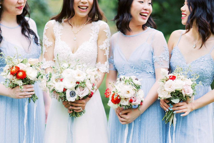bride and bridesmaids in light blue dresses carrying white and red bouquets