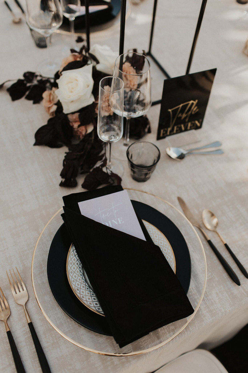 wedding place setting with black napkin and charger plate