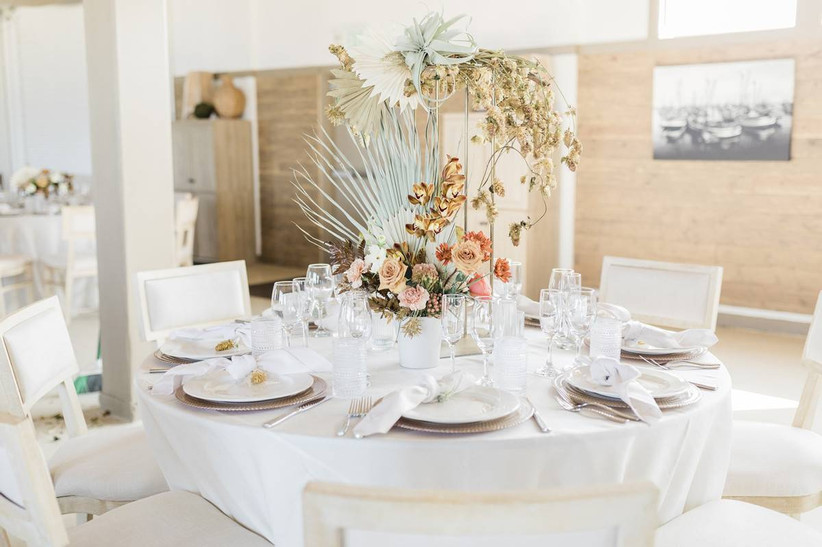 boho beach wedding centerpiece with painted palm leaves, air plants and orange orchids