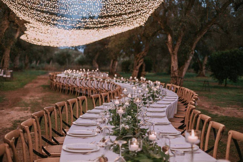 outdoor wedding reception long winding table trails through the forest with canopy of twinkle lights above it