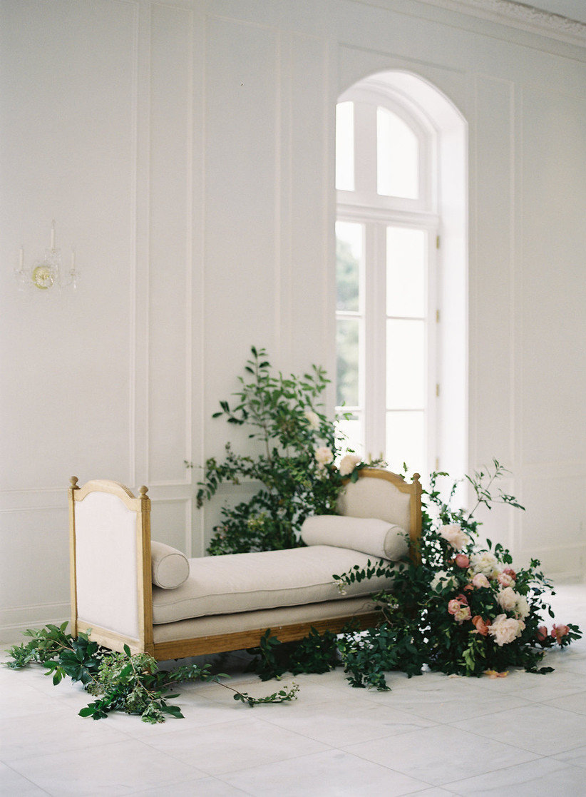 white upholstered French-style loveseat with abstract flowers and vines on the floor in front