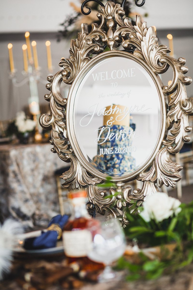 wedding welcome sign written onto mirror in decorative antique-style frame