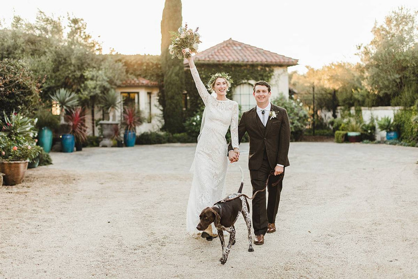bride and groom walking through gravel courtyard at sunset with their dog bride is raising one arm in the air holding her bouquet and smiling to the camera
