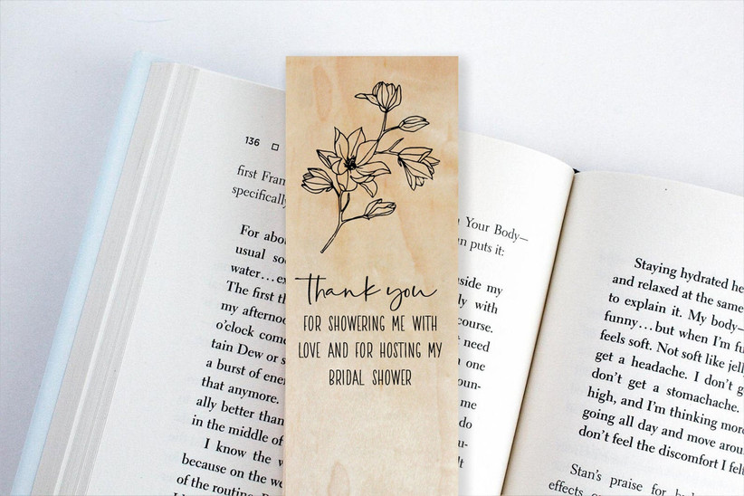 Wooden bookmark that reads Thank You for Showering Me With Love and for Hosting My Bridal Shower shown on pages of an open book
