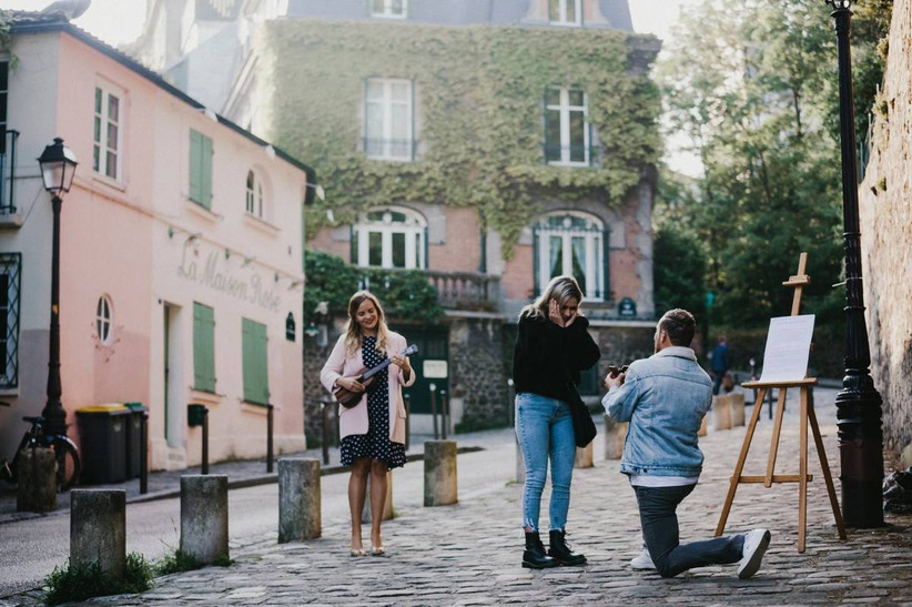 man proposing on one knee in paris cobblestone alley while guitarist stands nearby
