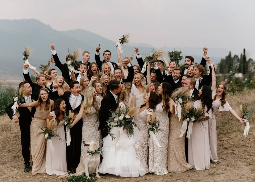 large wedding party cheering while bride and groom kiss