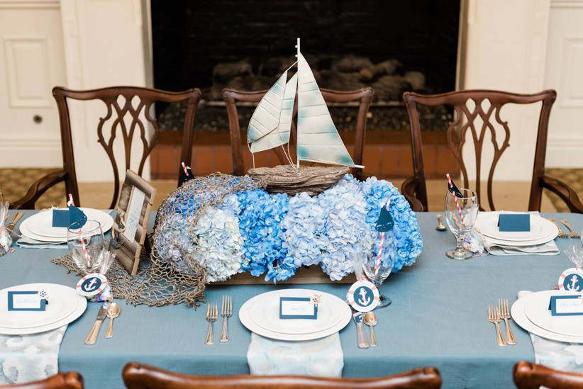 nautical beach wedding centerpiece with miniature sailboat on top of blue hydrangeas