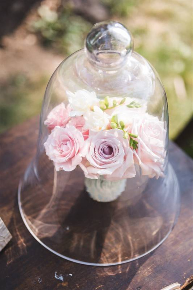 fairy themed wedding centerpiece with pink roses displayed in glass cloche jar