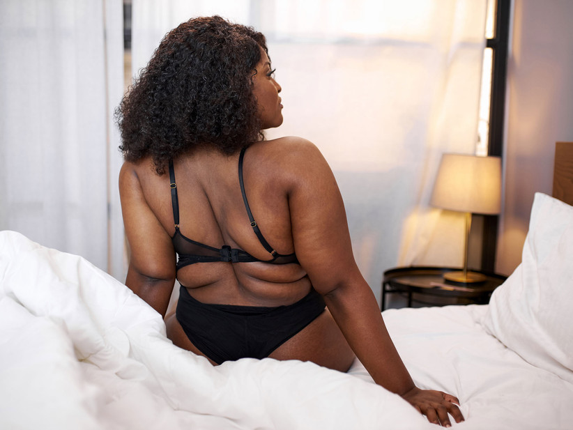 Black woman sitting on bed in black lingerie