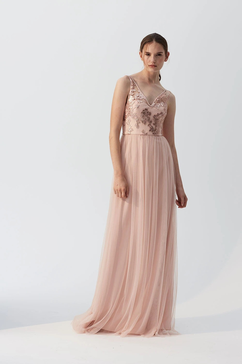 Model wearing blush pink tulle bridesmaid dress with sequined bodice
