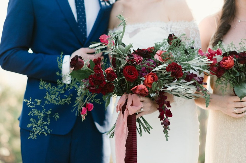 bride holds loose garden style bouquet with red flowers and greenery
