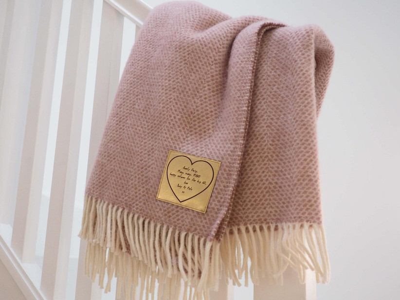 Pink-hued throw with fringe and stitched-on gold patch with personal message