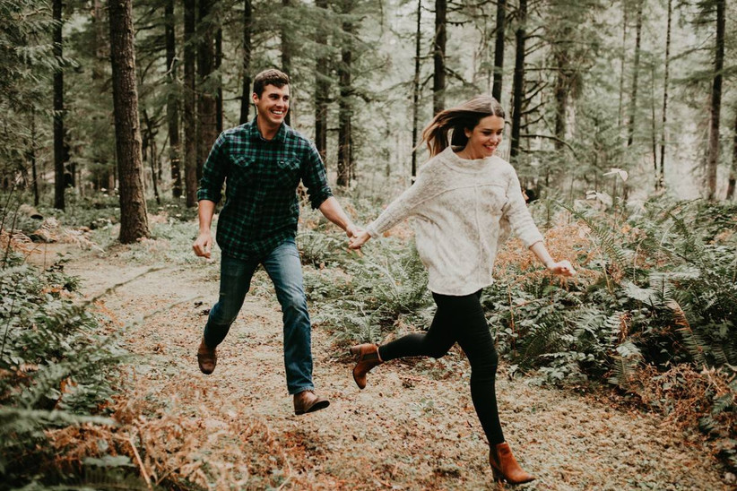 young couple holds hands as they run through a forest
