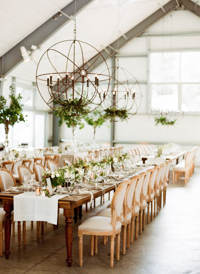 modern rustic wedding reception with bronze chandeliers above long wooden banquet tables