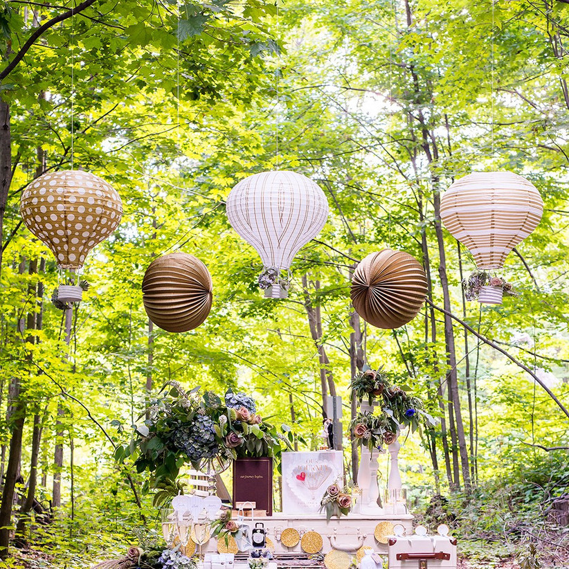 Outdoor proposal decoration setup with whimsical hot air balloon lanterns