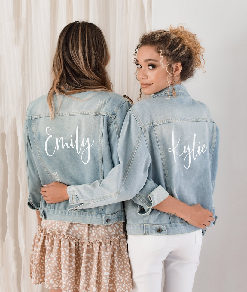 Two women wearing matching denim jackets personalized with their names