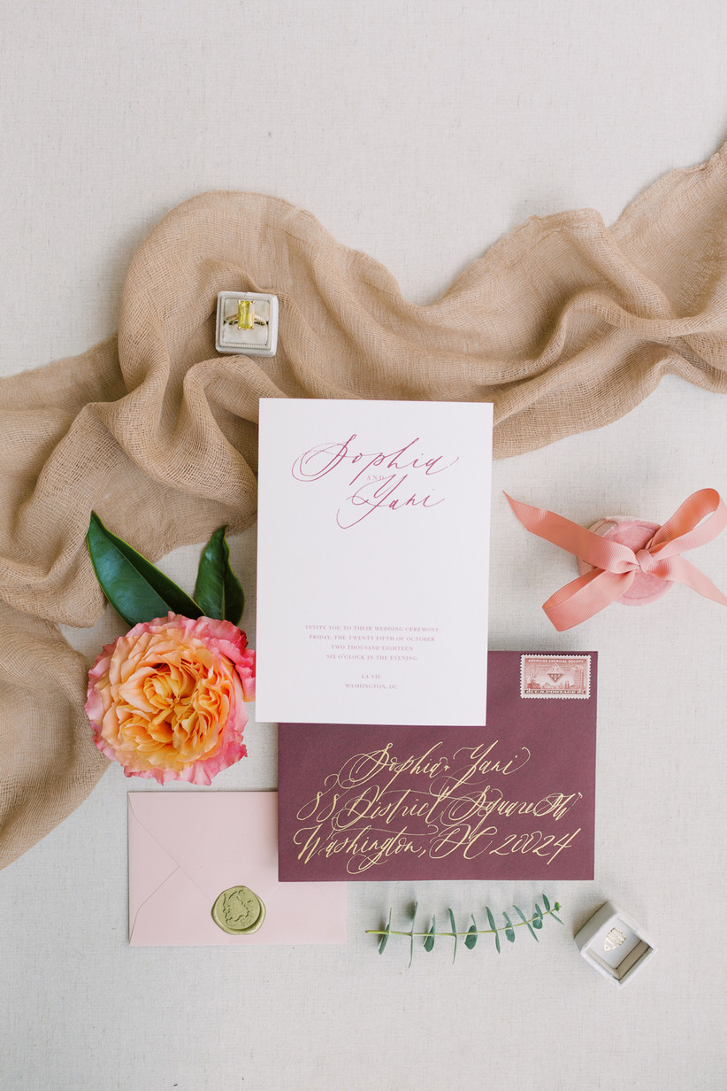 romantic wedding flat lay with pink and red stationery