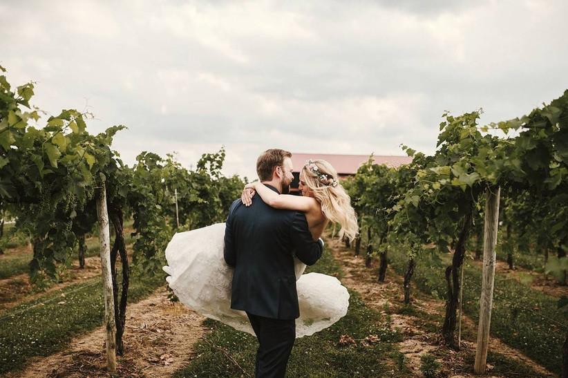 groom carries bride through vineyards
