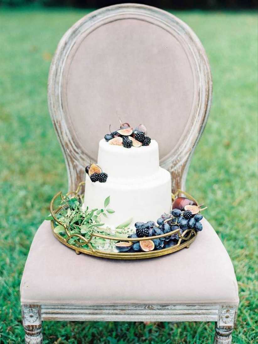 plain white wedding cake decorated with fresh blackberries, halved figs, and grape bundles