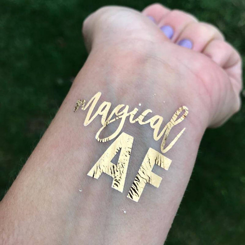 gold temporary tattoo on wrist that says