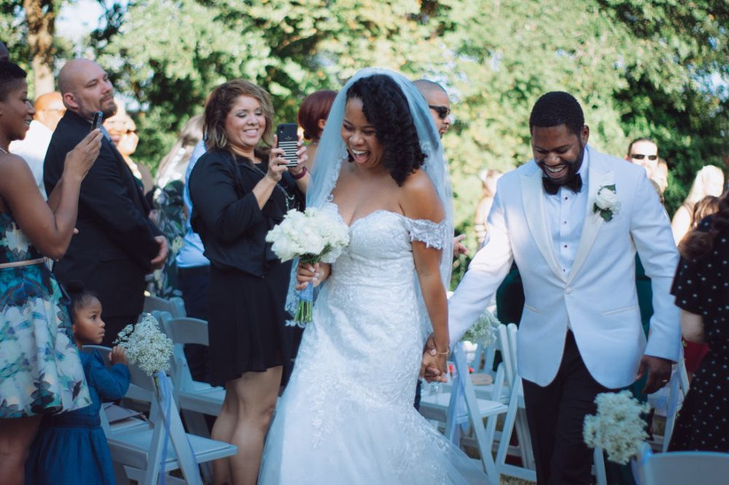 Newlywed couple celebrates as they walk down the aisle after exchanging vows