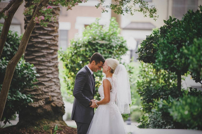 groom and bride kissing under palm trees