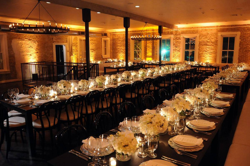 candle-lit wedding reception space with exposed brick walls, ceiling beams and rustic chandeliers