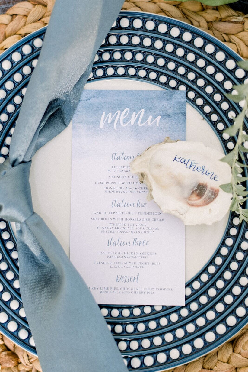 blue and white patterned dinner plate with blue watercolor menu card and oyster shell place card