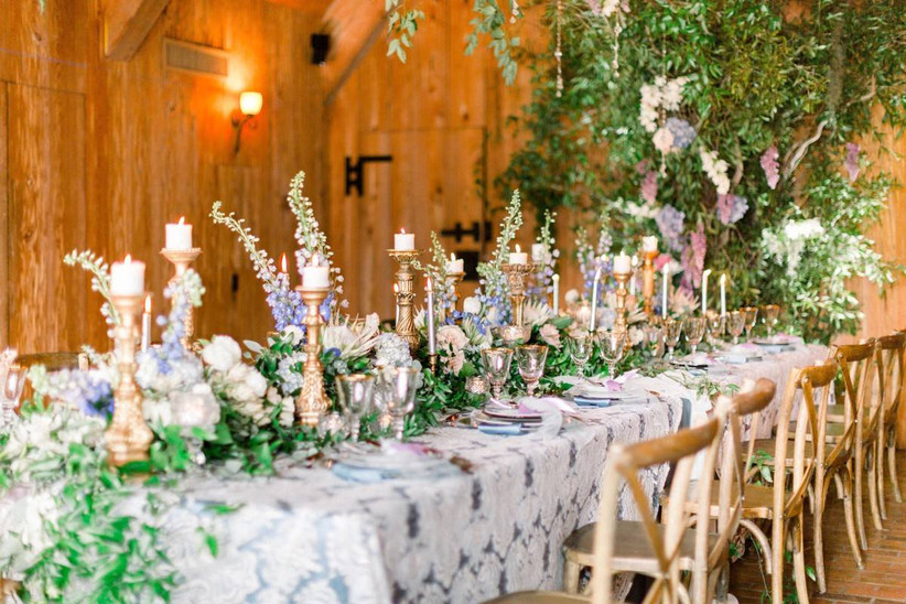 long reception table covered in lace tablecloth and overflowing with light pink, purple, and blue flowers accented with tall gold candle sticks