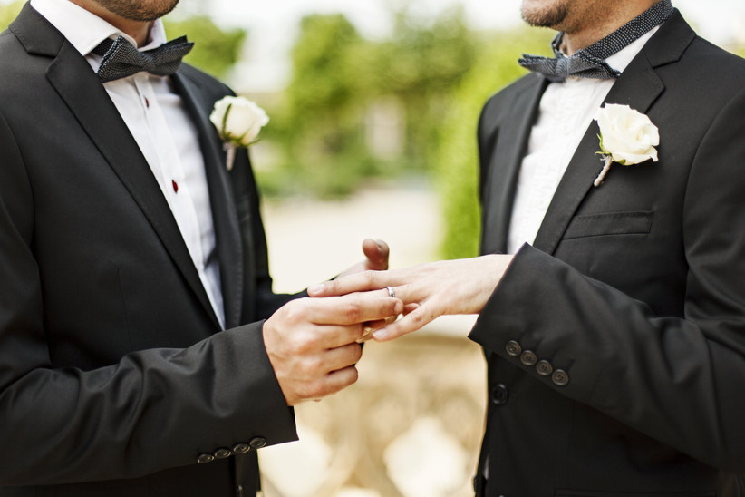 two grooms exchanging rings