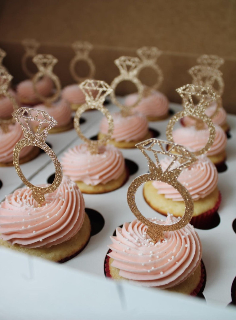 Pretty pink frosted cupcakes topped with engagement ring decorations