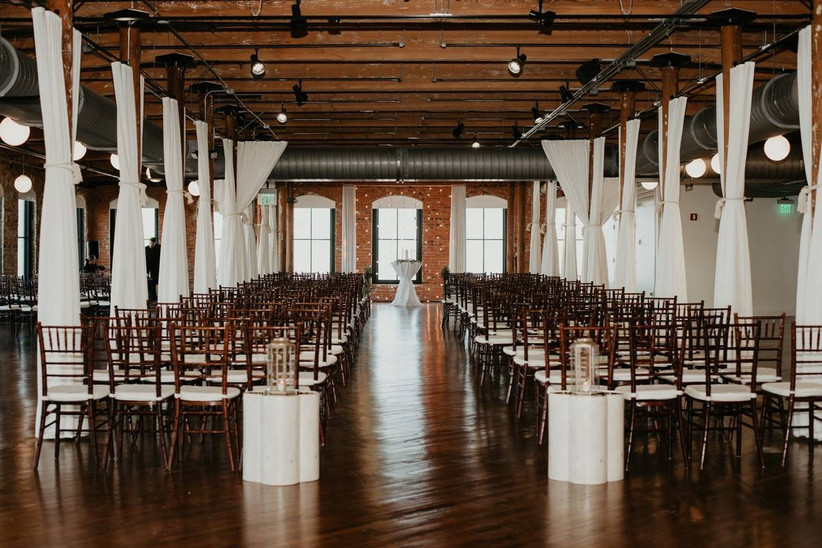 industrial wedding venue with white draping hanging from beam ceiling