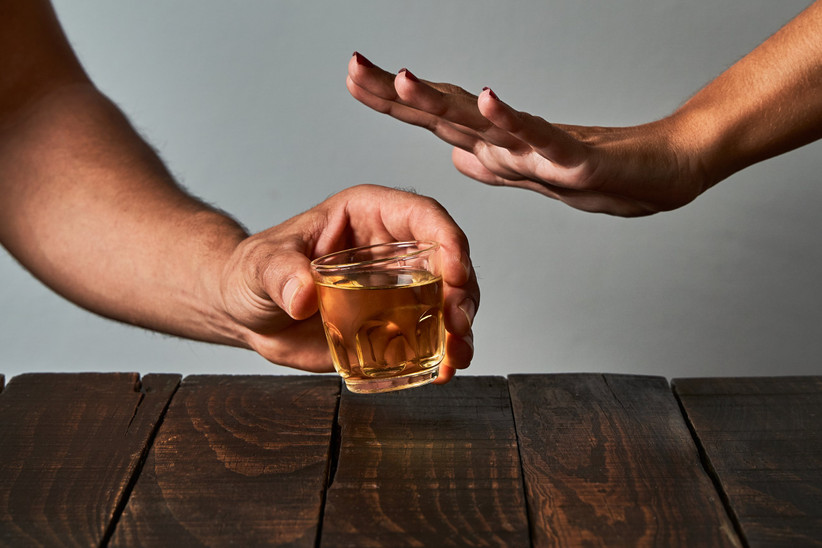 person holding shot glass while other person rejects it
