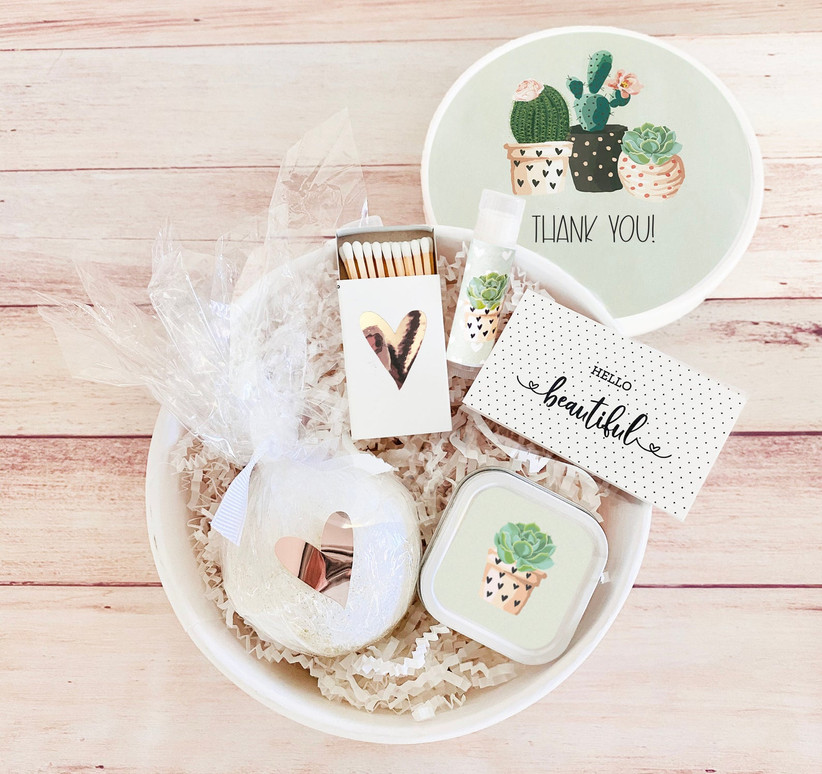 Round succulent-themed gift box with matches, a square tin candle, a bath bomb, lip balm, and a card reading Hello Beautiful