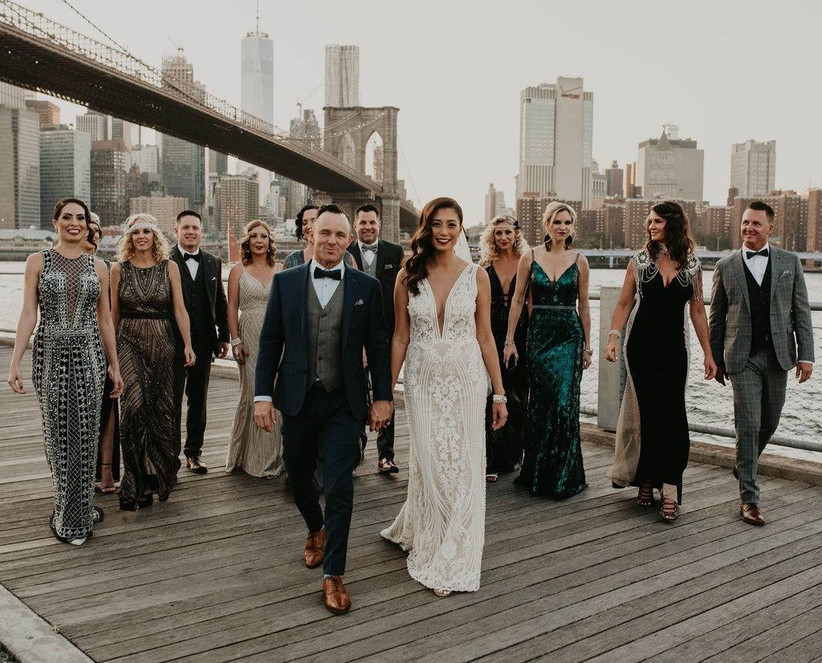 bride and groom walk outdoors under the brooklyn bridge with their wedding party who are dressed in tuxedos and sequin gowns
