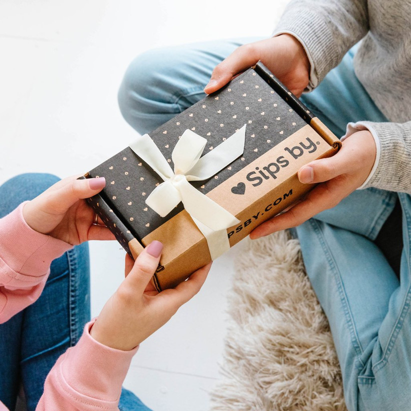 Hands exchanging a Sips by subscription box gift wrapped with a bow