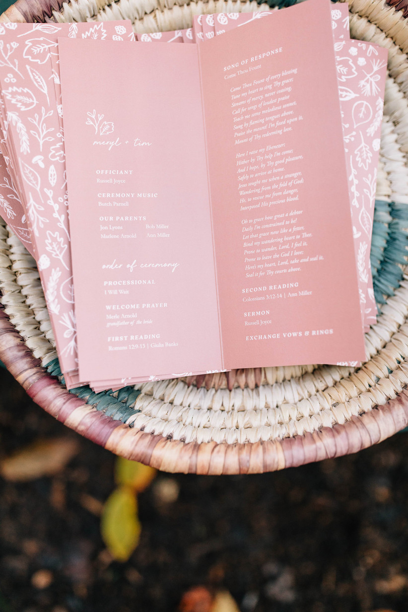 pink folded wedding ceremony card with white text