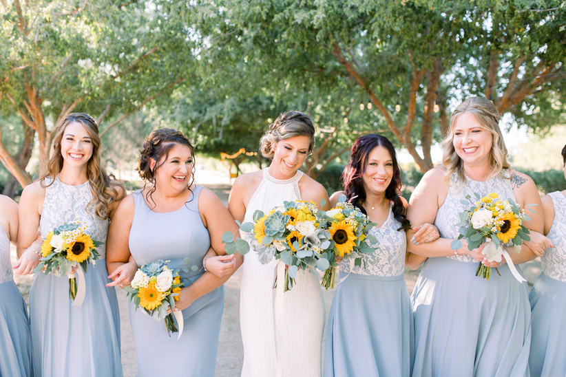 bride links arms with her bridesmaids who are wearing light blue gowns and holding yellow sunflower bouquets