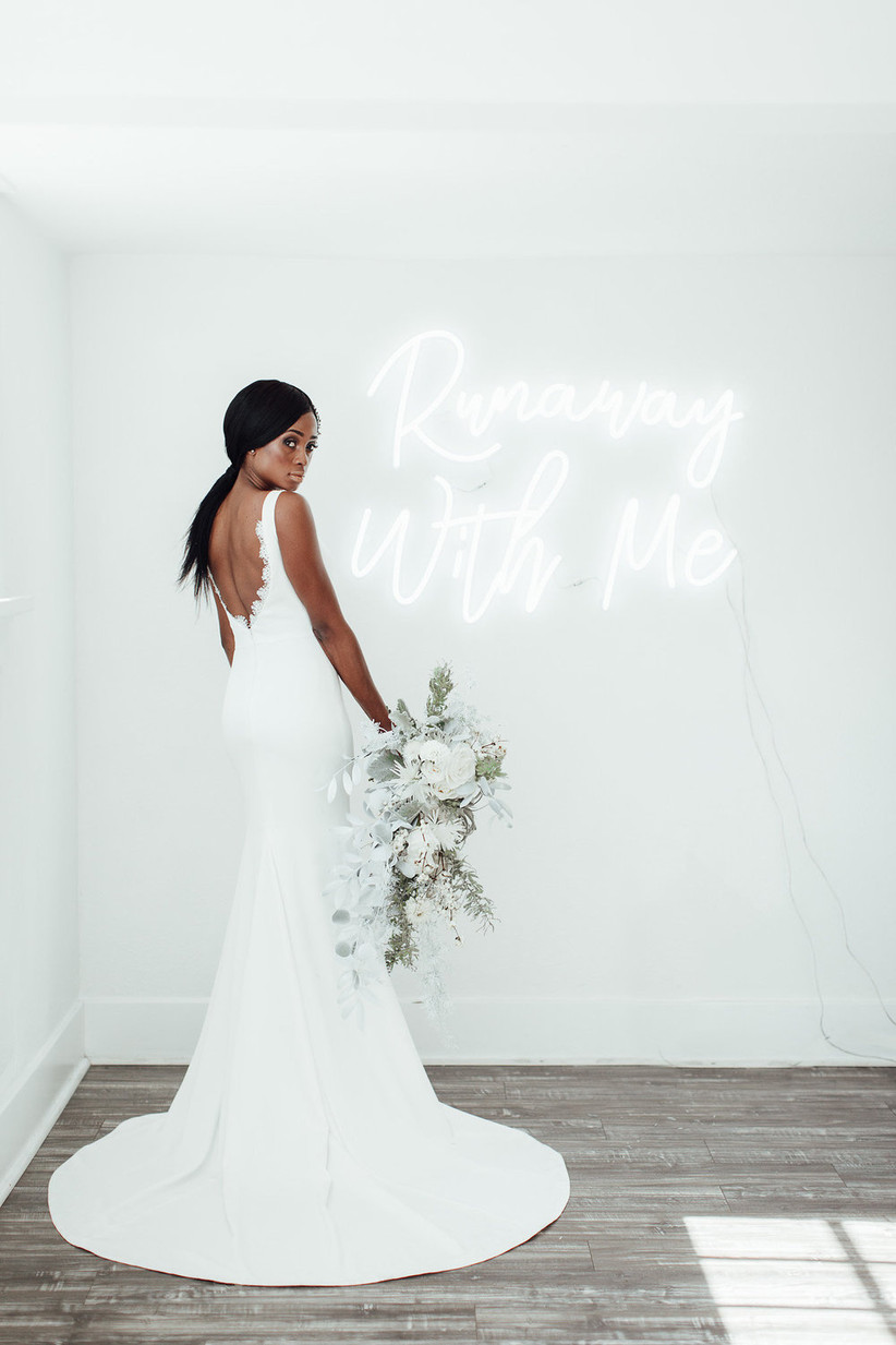 Black bride wears fitted wedding dress and holds a white and green bouquet while standing in front of a neon sign that reads