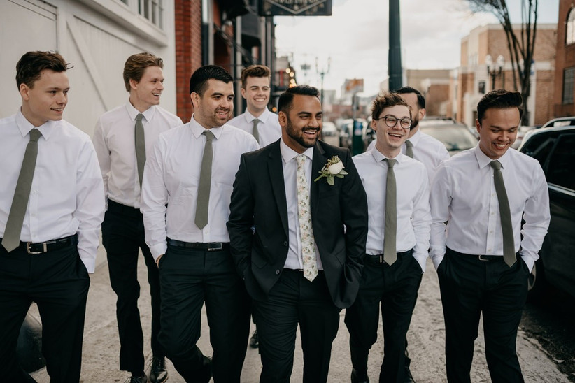 groom walking down the street with his groomsmen