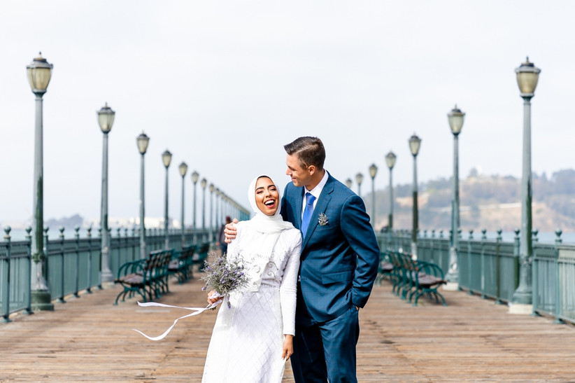 bride wearing hijab laughs with groom on san francisco pier