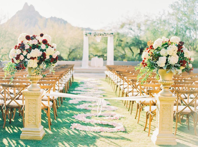 outdoor wedding ceremony with pink rose petals arranged in a swirling pattern down the grass aisle