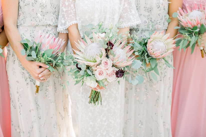 bride standing with bridesmaids carrying protea beach wedding bouquets
