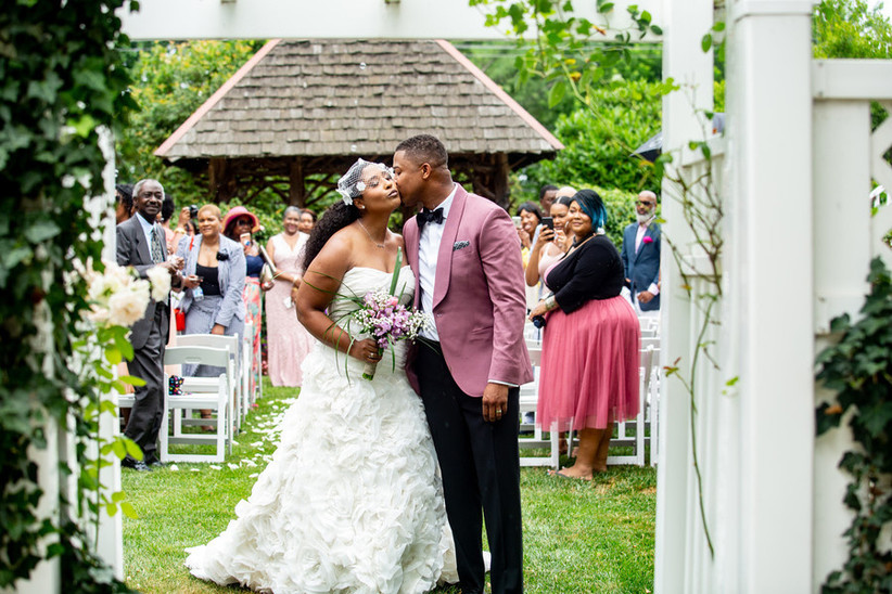Groom kissing bride on the cheek while guests stand in the background