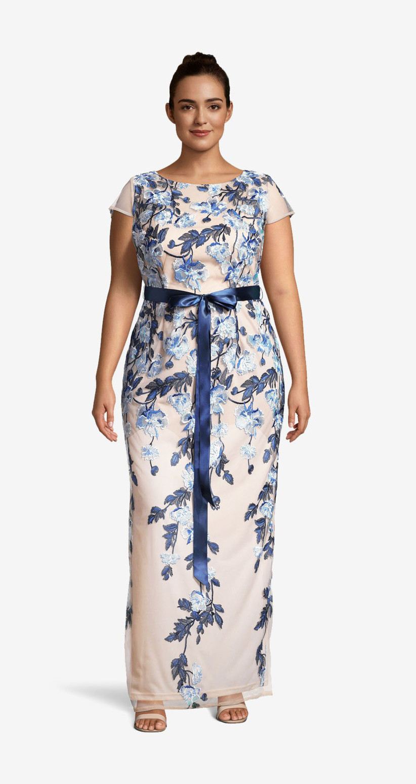 Model wearing nude column floor-length gown with beautiful light and dark blue floral pattern, sheer capped sleeves and blue ribbon around the waist
