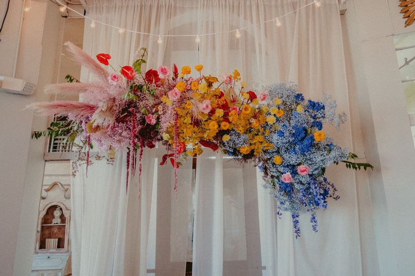 rainbow wedding theme hanging floral arch with ombre flowers in pink, yellow, orange, blue