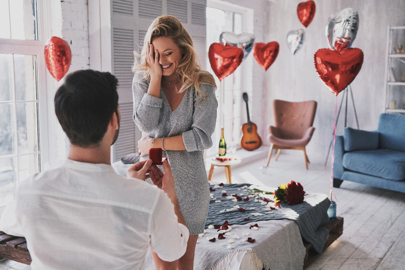Man proposing to woman at home with heart balloon decorations