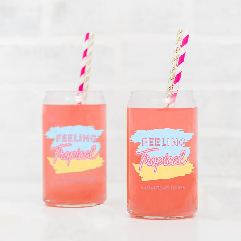 Two can-shaped drinking glasses that read Feeling Tropical personalized with names