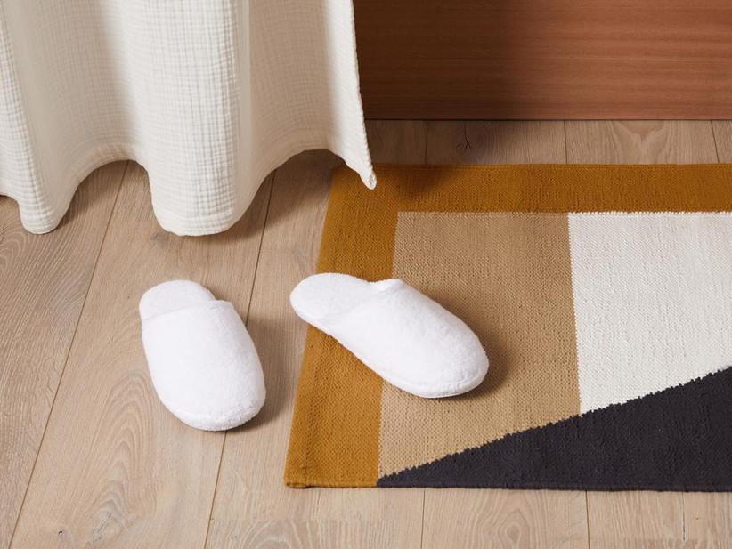 Snug white slippers on the floor next to fuzzy geometric rug
